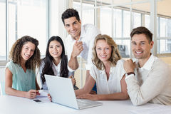 Casual business team having a meeting using laptop Stock Image