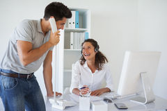 Casual business team laughing together at desk Royalty Free Stock Photography