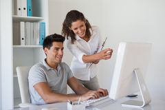 Casual business team looking at computer together at desk Royalty Free Stock Photography