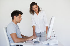 Casual business team looking at computer together at desk Royalty Free Stock Photo