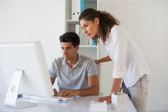 Casual business team looking at computer together at desk Royalty Free Stock Images