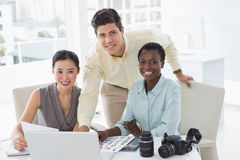 Casual business team looking at laptop together Stock Images