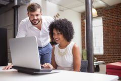 Casual business team looking at laptop together Royalty Free Stock Image