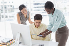 Casual business team looking at tablet together Royalty Free Stock Images