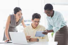 Casual business team looking at tablet together Royalty Free Stock Image