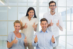Casual business team showing thumbs up to camera Stock Images