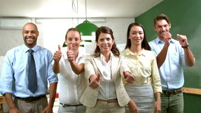 Casual business team showing thumbs up to camera stock video footage