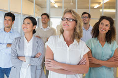 Casual business team smiling with arms crossed looking up Royalty Free Stock Photos