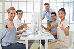 Casual business team smiling at camera showing thumbs up Royalty Free Stock Photo