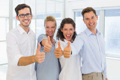 Casual business team smiling at camera and showing thumbs up Stock Photos