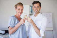 Casual business team smiling at camera toasting with champagne Royalty Free Stock Photography