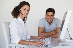 Casual business team smiling at camera together at desk Stock Photo