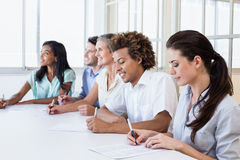 Casual business team taking notes in meeting Royalty Free Stock Photos