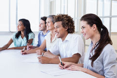 Casual business team taking notes in meeting Stock Photo