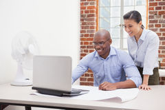 Casual business team using laptop at desk Stock Photos