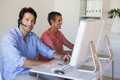 Casual business team working at desk using computers with man smiling at camera Royalty Free Stock Photo