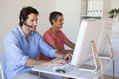 Casual business team working at desk using computers with man using headset Royalty Free Stock Photography
