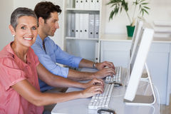 Casual business team working at desk using computers Royalty Free Stock Images
