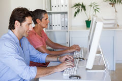 Casual business team working at desk using computers Stock Images