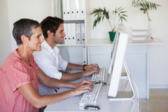 Casual business team working at desk using computers Stock Photography