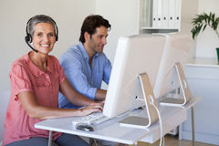 Casual business team working at desk using computers with woman using headset Royalty Free Stock Photos