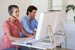 Casual business team working at desk using computers with woman using headset Royalty Free Stock Images