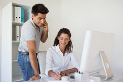 Casual business team working together at desk Stock Images