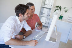 Casual business team working together at desk using computer Stock Photos