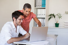 Casual business team working together at desk using laptop Royalty Free Stock Photos