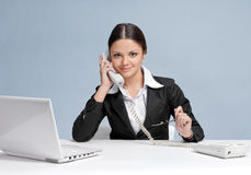 Casual business woman in office talking by phone Royalty Free Stock Photo