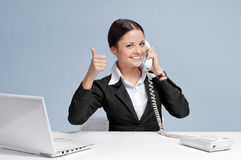 Casual business woman in office talking by phone. Casual business woman in office working with white table, laptop and talking by phone. Thumbs up Stock Photos