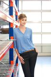 Casual business woman standing in warehouse Stock Images