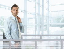 Casual businessman. Standing in front of glass walls in office lobby, smiling stock photography