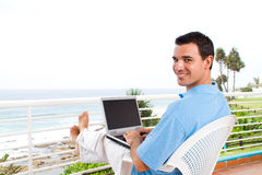 Casual businessman. Using laptop on balcony with sea view behind during holiday Royalty Free Stock Photos