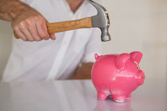 Casual businessman breaking piggy bank with hammer Stock Photography