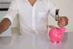 Casual businessman breaking piggy bank with hammer Stock Photo