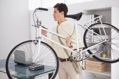 Casual businessman carrying his bicycle Royalty Free Stock Photos