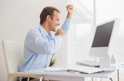 Casual businessman cheering at his desk Royalty Free Stock Photo