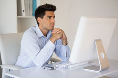 Casual businessman concentrating at his desk Stock Photo