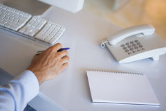 Casual businessman at desk with notepad and telephone Stock Image