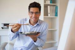 Casual businessman enjoying sushi at his desk Royalty Free Stock Image