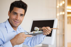 Casual businessman enjoying sushi at his desk Royalty Free Stock Photos