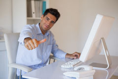 Casual businessman giving thumbs up to camera at his desk Stock Image