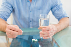 Casual businessman holding glass of water and tablet Royalty Free Stock Images