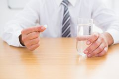 Casual businessman holding glass of water and tablet Stock Photography