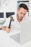 Casual businessman holding hammer over laptop Royalty Free Stock Images