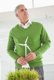 Casual businessman holding model wind turbine Royalty Free Stock Image