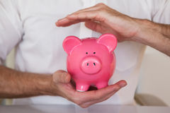Casual businessman holding piggy bank Royalty Free Stock Images