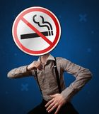 Businessman holding no smoking sign. Casual businessman holding round sign with no smoking graphic stock photography