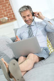 Casual businessman with laptop working on sofa Royalty Free Stock Photography
